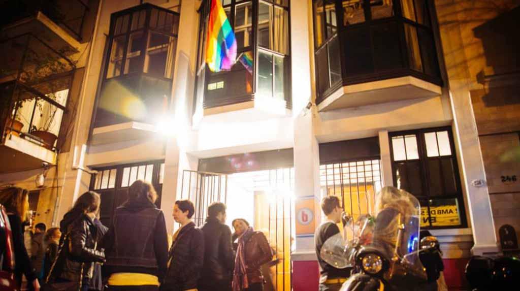 Casa Brandon: a fachada com bandeira LGBT pendurada, as pessoas na rua conversando.