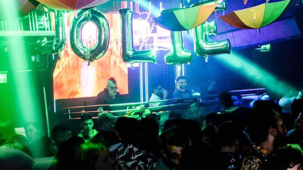 Fiesta Jolie: DJ e pessoas dançando com luzes colorindo o ambiente.