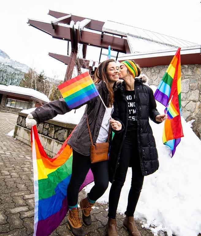 Mulheres segurando a bandeira LGBT