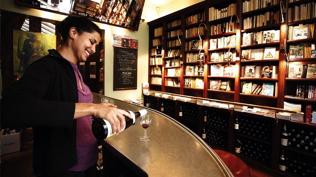 La Belle Hortense misto de livraria e bar, moça servindo uma bebida em frente a uma estante de livros