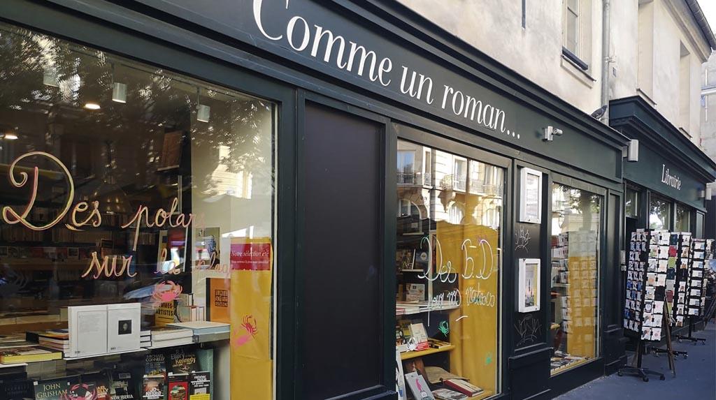 Fachada da livraria Comme un roman, painel verde com nome em branco